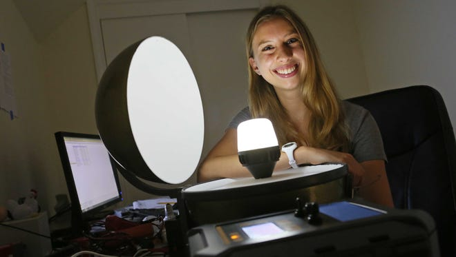 Sarah Morrissey, a pre-veterinarian medicine and animal biosciences graduate from the University of Delaware, sits with a light used in broiler chicken houses. For her senior thesis, Morrissey created an online tool that poultry farmers can use to determine the best combination of lights and dimmers for their chicken houses.