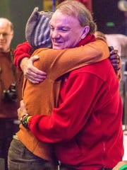 Tim McLoone of Holiday Express hugs a guest at one
