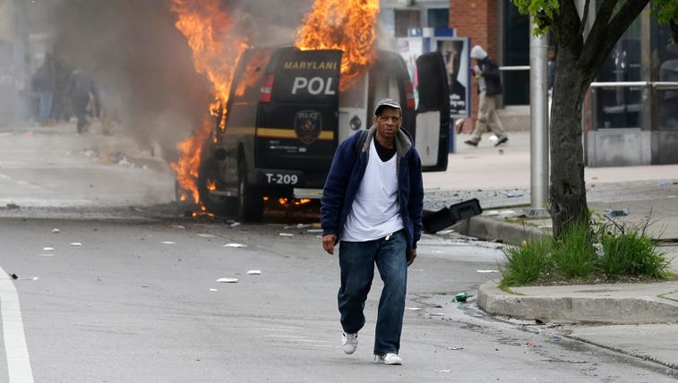 A man walks past a burning police vehicle, Monday,