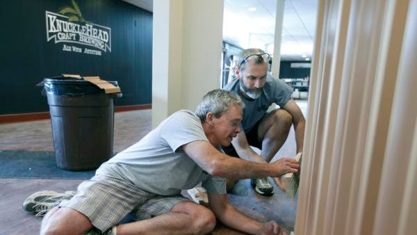 Co-founders Len Dummer, left, and George Cline work on remodeling Knucklehead Brewery in Webster. The founders hope to open this fall.