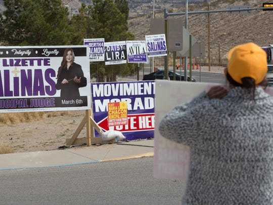 A supporter of Maria Chacon stands with a sign near signs for other candidates Lizette Salinas, Daisy Lira, Bertha Salmon and Jessica Aliva in  Sunland Park municipal elections, Tuesday March 6, 2018 in Sunland Park.
