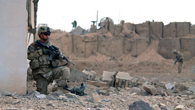U.S. soldiers inspect the scene of a suicide attack outside a base in Zhari district, Kandahar province, Afghanistan, on Jan. 20.