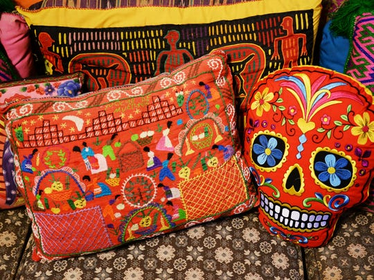 Folk art pillows from Lee Spruell's home depict Day of the Dead art.