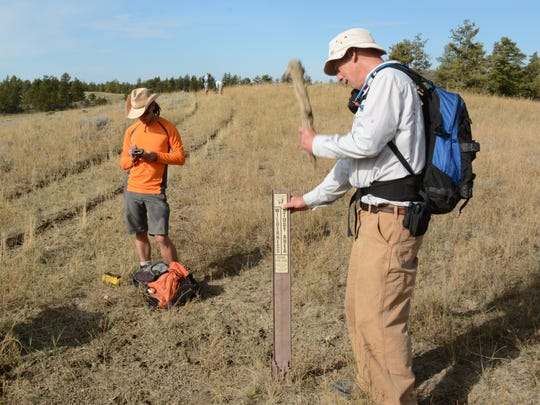 Volunteer Tom Javins reinstalls a damaged Bureau of Land Management sign while Jesse Bergeson records a GPS location. The two were surveying Wilderness Study Areas in the Upper Missouri Breaks National Monument.