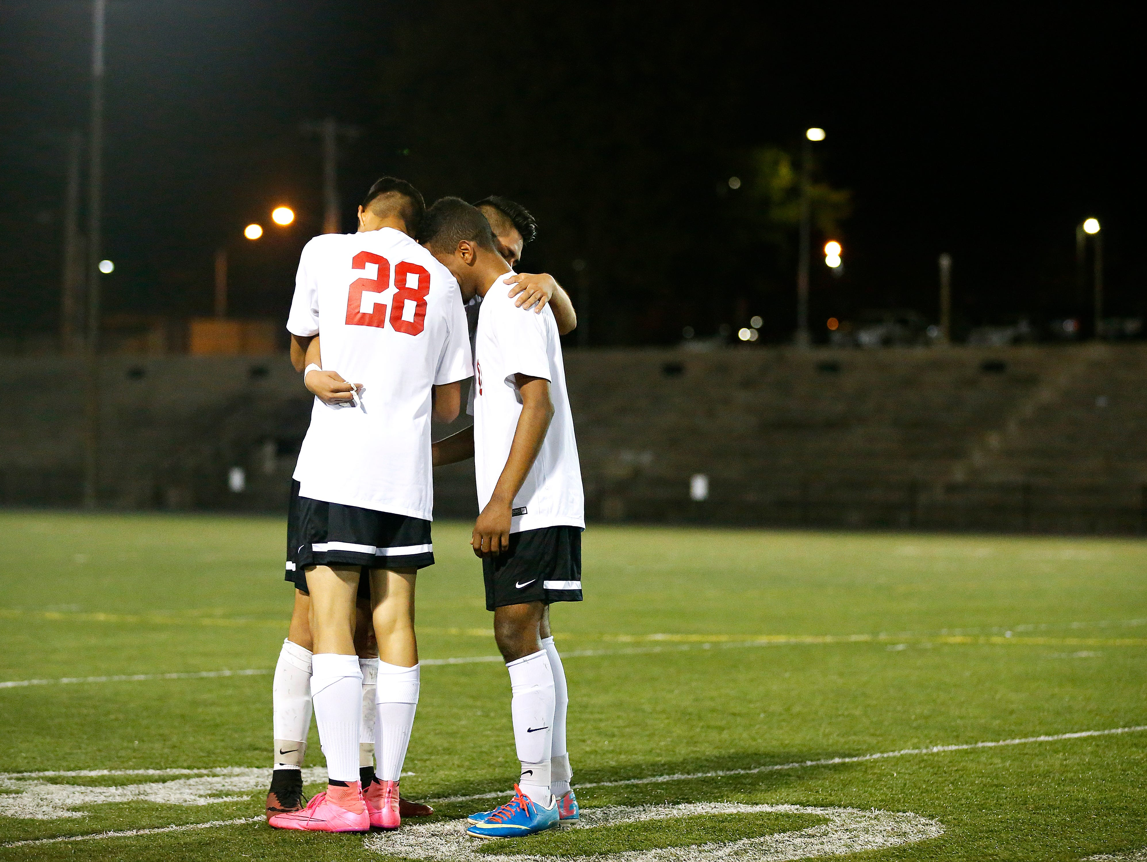 Central High School players Gerardo Botello (28) Manny Torres (11) and Ally Mohamed (10) console each other after the Bulldogs sectional playoff loss against the Nixa Eagles at Harrison Stadium in Springfield, Mo. on Nov. 3, 2015.