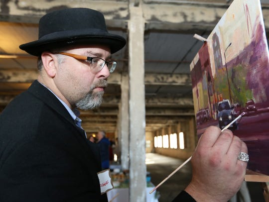 FILE - Jason Prigge works on a painting of downtown Manitowoc.