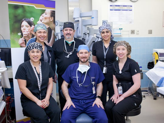 The surgical team prior to live telesurgery: Top row, from left,  Dr. Jessica Compean (anesthesia), Lorenzo Del Olmo (licensed surgical assistant) and Maggie Silva (surgical tech). Bottom row: Clarissa Anderson (surgical tech), Dr. Richard Farnam director of Robotic Epicenter) and  Valeria Torres (RN).