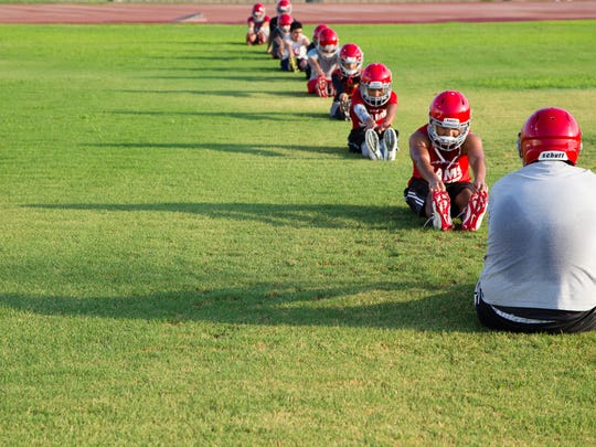 The Desert Mirage High School football team stretches before pre-season practice on Monday, August 1, 2016.