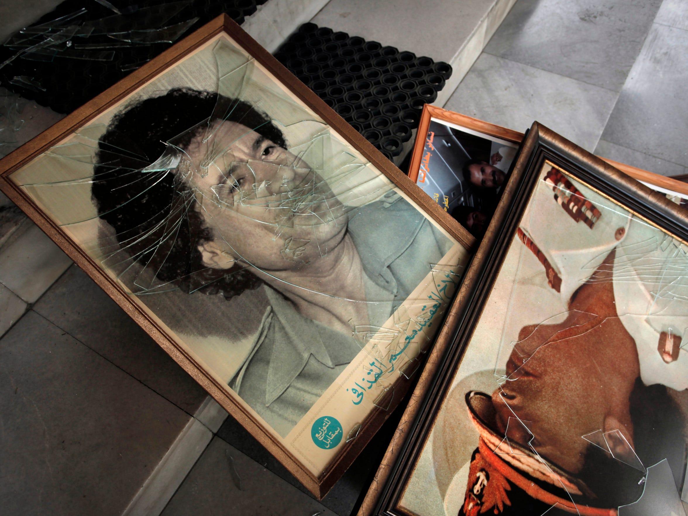 Broken portraits of Moammar Gadhafi seen at the Libyan