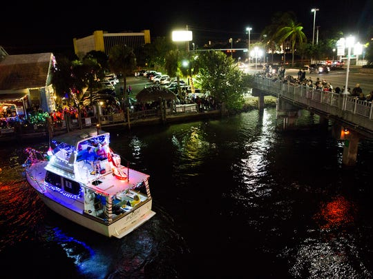 """Boat number eight turns around at the end of the parade line during the Naples Boat Parade on Saturday, December 10, 2016 in the city of Naples. Boaters were encouraged to decorate their boats along with the """"super hero"""" theme for the 27th annual parade."""