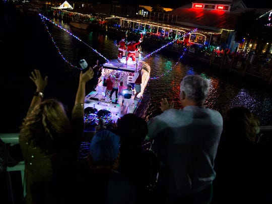 "People wave and dance to music coming from a boat during the Naples Boat Parade on Saturday, December 10, 2016 in the city of Naples. Boaters were encouraged to decorate their boats along with the ""super hero"" theme for the 27th annual parade."