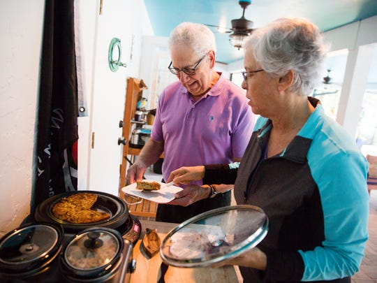 """Stan Samuelson and Elinor Saltz, visiting from Cape Cod, Mass., grab a serving of a vegan, gluten-free quiche for breakfast at the 3-acre retreat Pirate Palms on Friday, Jan. 13, 2017, in Golden Gate Estates. The """"edible landscape"""" of Pirate Palms help to teach guests about healthy eating and exercise."""