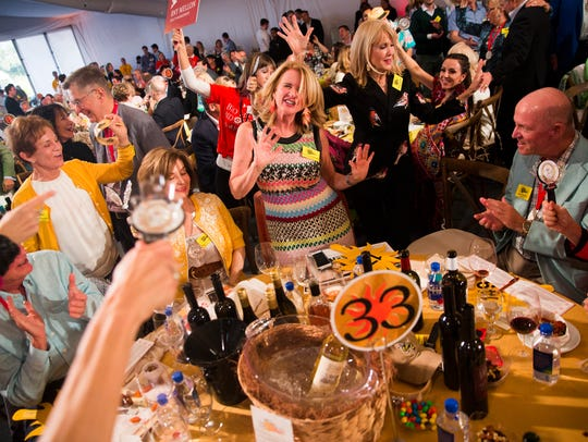"""Ann Welsh McMulty dances after winning Lot 54 during the """"Bright Sunshiny Day"""" Auction at the Naples Winter Wine Festival on Jan. 28, 2017."""