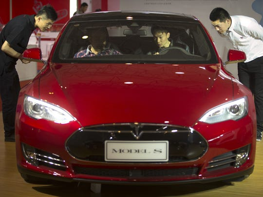 In 2016: Staff members talk with visitors as they sit inside a Tesla Model S electric car on display at the Beijing International Automotive Exhibition in Beijing in April 2016.