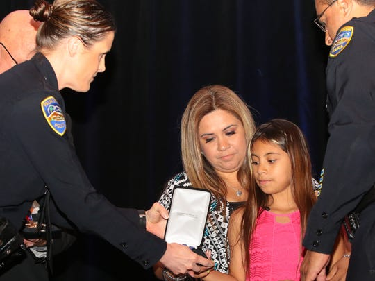 Vanessa Vega receives the Medal of Valor for her father, Jose 'Gil' Vega, at the Palm Springs Police and Fire Awards luncheon, Tuesday, April, 18, 2017.  Officer Vega was one of two officers who was killed when responding to a family disturbance at a Palm Springs home in October.