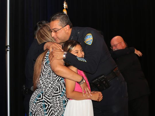 Bryan Reyes embraces Vanessa Vega after presenting her with a Medal of Valor that was awarded to her father Officer Jose 'Gil' Vega, at the Palm Springs Police and Fire Awards luncheon, Tuesday, April, 18, 2017.  Officer Vega was one of two officers that was killed in October when responding to a family disturbance at a Palm Springs home.