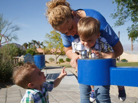 Electra Viveros givers her son Talen a lift up to the water fountain at a La Quinta park as her son Luca looks on, April 5, 2017.