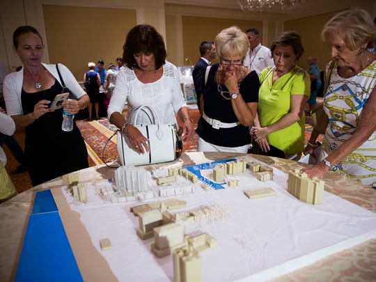 Residents discuss the development over a 3-D rendering of the property during an open house on Wednesday, May 17, 2017, at the Ritz Carlton beach resort in North Naples. Vanderbilt Holdings LLC, an affiliate of Stock Development, wants to develop a project called One Naples that would include Stock Development's first high-rise, an 18-story condo building over three levels of parking.