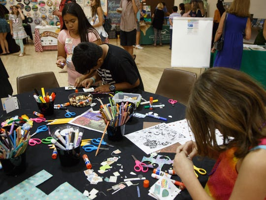 Erika and Alex Miranda, center, make books at a crafts