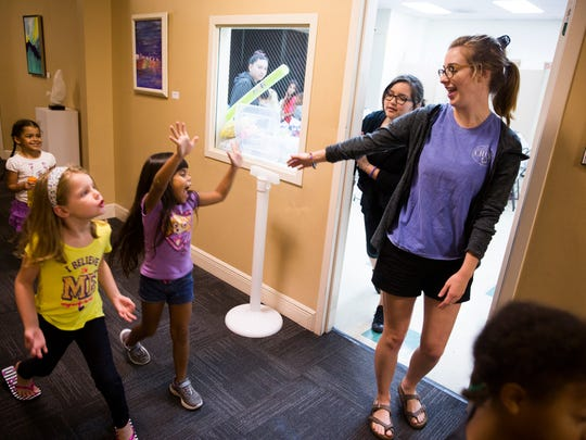 Kathleen Gieselman, an intern, reaches out to greet some of the students on Tuesday, June 20, 2017, during summer camp at Center for Performing Arts Bonita Springs.
