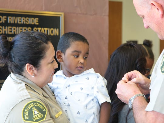 Sheriff's Deputy Alicia Lopez holds Matthew Castleberry, Jr., as he is given a pin during a media event at the Riverside County Sheriff's Department in Palm Desert, Calif., Tuesday, July 11, 2017.  Alicia will be donating her kidney to three-year-old Matthew who suffered severe damage to his bladder and kidneys from Posterior Urethral Valves.