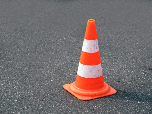 traffic cone, white and orange  on gray asphalt, copy space