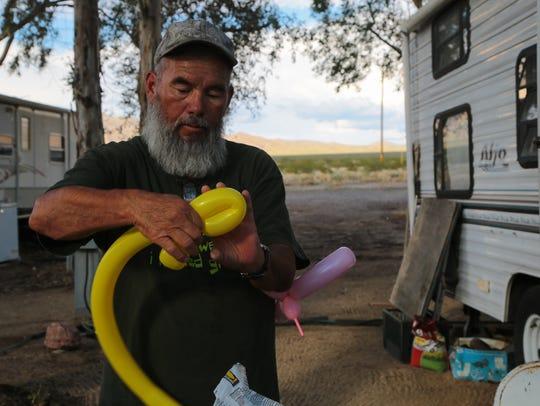 Al Fierro makes balloon scupltures outside of his trailer