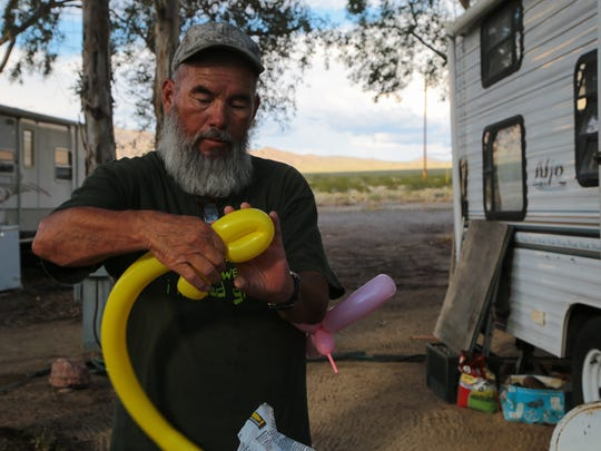 Al Fierro makes balloon scupltures outside of his trailer in Nipton, Calif., Wednesday, August 2, 2017.  Al stays in Nipton during the week when working at the nearby Ivanpah Solar Facility.