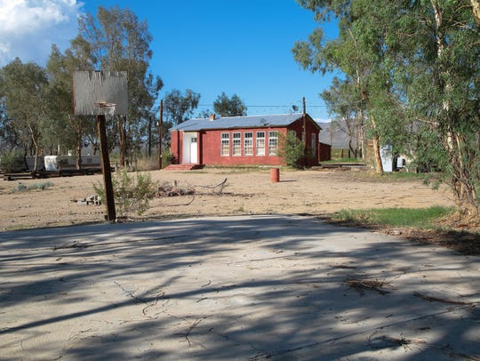 A basketball court sits next to the old schoolhouse