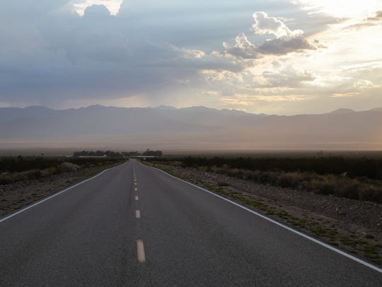 A two-lane road running through the Mojave Desert toward