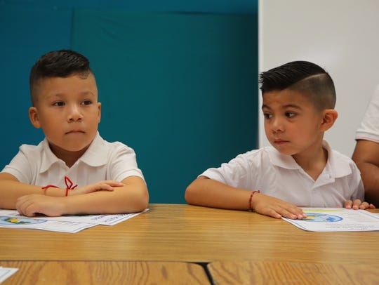 Kindergarteners find their seats on the first day of