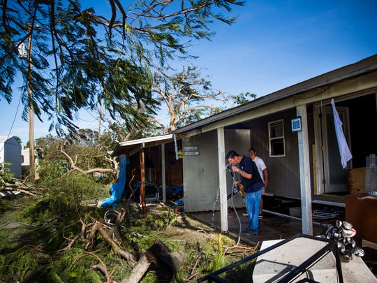Norm, a resident of Chokoloskee, sips from a water hose as he helps his neighbor, Michael Kelley, clean up his home after on Monday, September 11, 2017 in Chokoloskee after Hurricane Irma.
