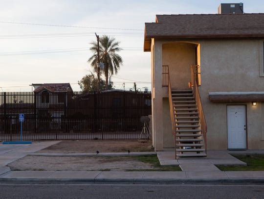 A section of the border wall stands next to homes in