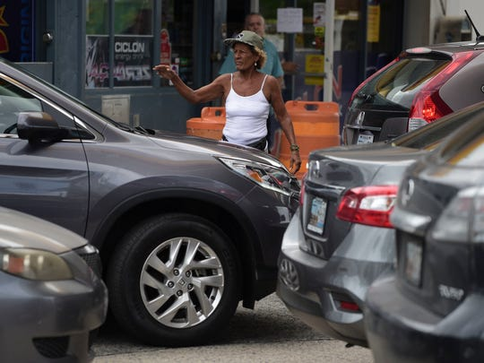 A woman directs drivers lining up to buy gasoline at a gas station on Tuesday,  one day before the forecasted arrival of Hurricane Maria in San Juan, Puerto Rico.