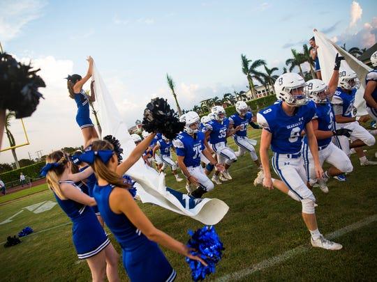 The Community School of Naples varsity football team runs onto the field on Friday, September 22, 2017 at Community School of Naples during the game against Moore Haven High School.