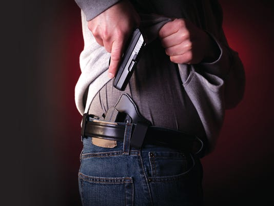 A person concealing their pistol on their hip