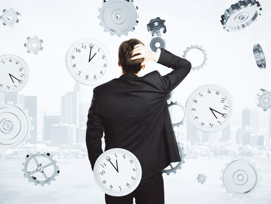Clocks surround businessman Stock