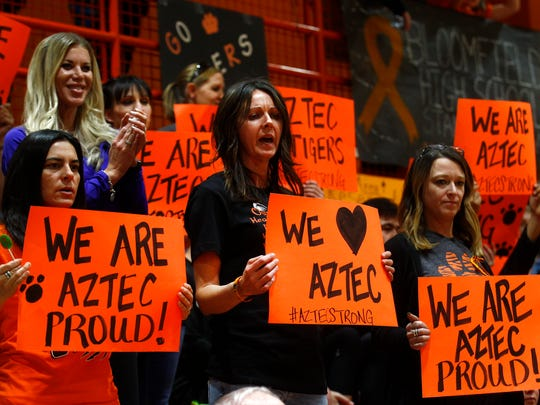 Aztec High School supporters hold up signs for their boys basketball team before the start of a game against Piedra Vista on Thursday at Lillywhite Gym in Aztec. The contest was the team's first since a deadly shooting took place at the school on Dec. 7.