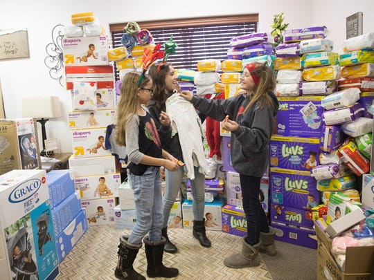 Cozy Christmas volunteers Jadyn Gardenhire, left, Kayleigh Roquemore and Maggie Magee look over items they helped raise with their friend Taylor Clugston on Friday at the Grace Place Pregnancy and Health Center in Farmington.