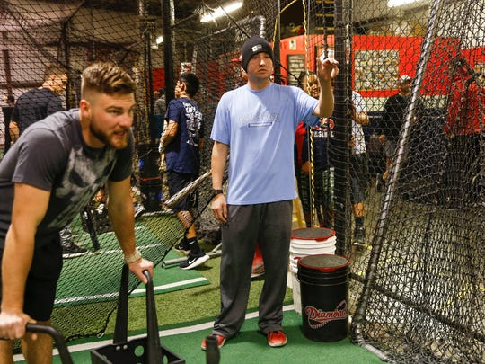 Justin Solomon works helps coach young players Wednesday at The Strike Zone in Farmington.