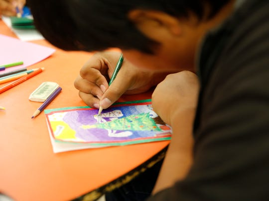 Newcomb Middle School eighth-grader Albert Lapahie colors a Christmas tree he drew on a card for a resident at the Chinle (Ariz.) Nursing Home.