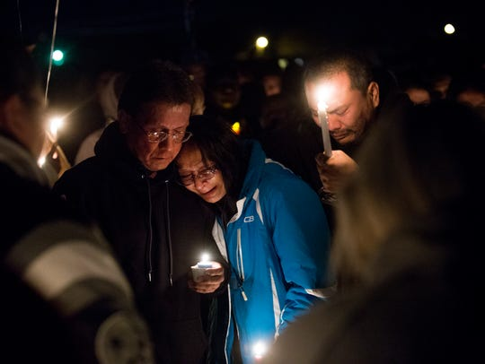 Charles Sam, left, and Anna Sam mourn the loss of Mitchual Sam and Hjordis Sam during a candlelight vigil on Friday in Kirtland.