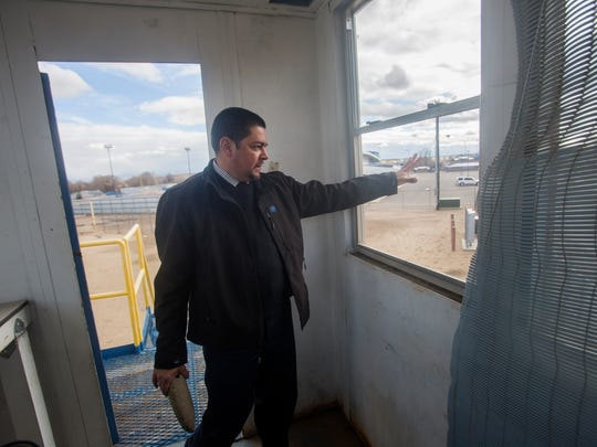 James Olivas, director of data, operations and assessment for the Bloomfield Municipal School District, shows a broken window inside the softball practice field press box during a tour on Wednesday Bloomfield High School.