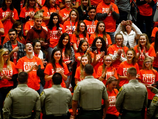 Students applaud members of the San Juan County Sheriff's Office during a school assemblyon Friday at Lily White Gym at Aztec High School.