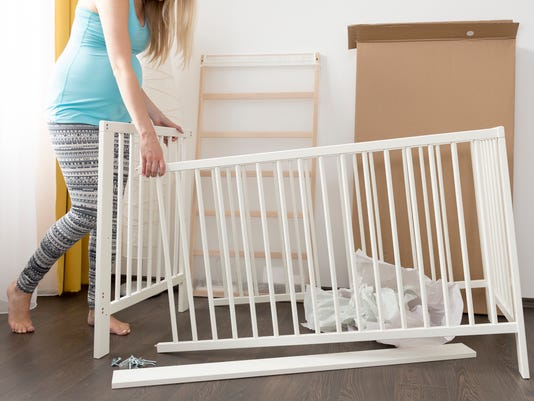 pregnant woman assembling bed for expectant baby