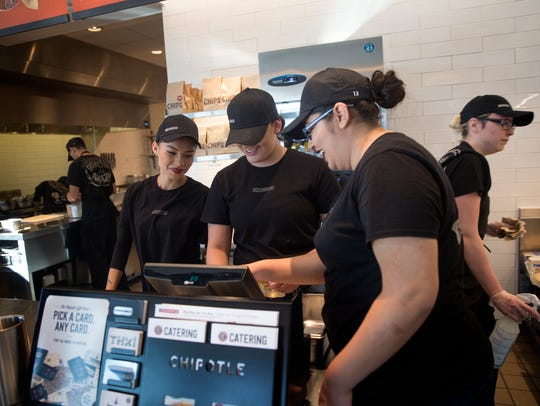 Cashier Aaliyah Wilson, left, watches as trainers Emmri Tafoya and Santiara Figueroa use the cash register on Wednesday at Chipotle in Farmington.