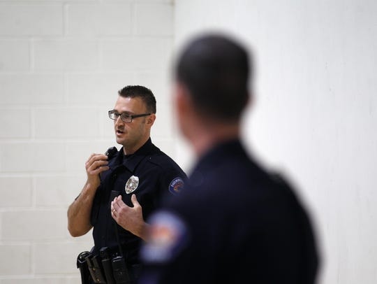 Farmington Police Department Det. Chris Stanton, left, and Cpl. Travis Spruell talk about local gang activity during a presentation on Thursday at the Sycamore Park Community Center in Farmington.