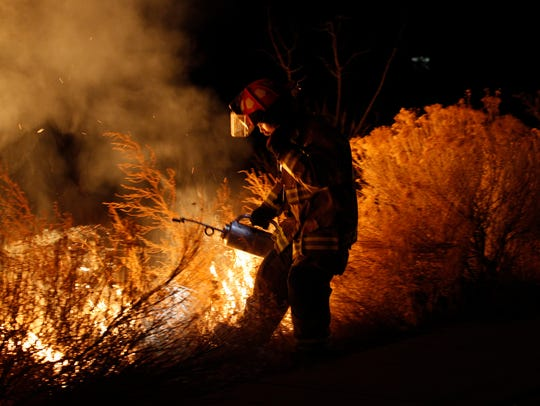 A member of the San Juan County Fire Department sets a back burn on Jan. 20 as crew members work to contain a wildfire in Bloomfield that was sparked by fireplace ashes.