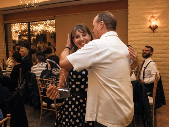 Jamie Church hugs her husband Darrin Church on Friday after earning the Farmington Chamber of Commerce's citizen of the year award at the San Juan Country Club in Farmington.