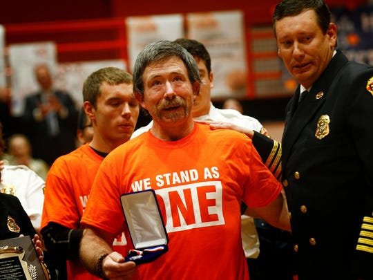 """Aztec High School custodian and volunteer firefighter Thomas """"Emery"""" Hill, left, is honored with the Medal of Valor by San Juan County fire Chief Craig Daugherty during a school assembly on Jan. 12 at Lillywhite Gym at the school."""